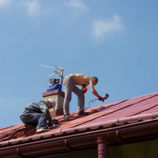two people paint a roof